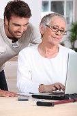 Man helping old lady with computer
