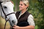 stock photo of fillies  - Young lady stroking her horse - JPG