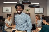 Portrait of happy african businessman looking at camera and sitting at desk. Mature business man in  poster