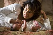 stock photo of tickle  - African American mother admiring her newborn child - JPG