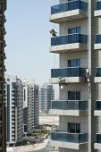 Three High-rise Workers Wash Windows Of A High-rise Building In Dubai poster