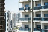 High-rise Workers Wearing Seat Belts Wash The Windows Of A High-rise Building In Dubai poster