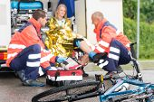 stock photo of ambulance car  - Accident bike woman get emergency help paramedics in ambulance - JPG