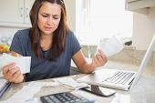 image of count down  - Young woman getting stressed over finances in kitchen - JPG