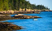 picture of off-shore  - A lonesome small boat floating all alone on the jagged shore off the coast of Main in Acadia National Park with the blue sky and water surrounding it - JPG