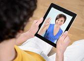 picture of video chat  - Man and woman communicate through video chat on modern apple ipad - JPG
