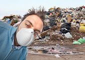 stock photo of landfill  - Young boy with mask respiratory protection near landfill - JPG
