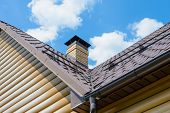 pic of downspouts  - chimney on the roof of the house against the blue sky - JPG