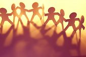 stock photo of collaboration  - Team of paper doll people holding hands - JPG