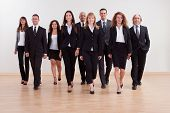 pic of self-employment  - Large diverse group of business executives approaching walking towards the camera led by a smiling woman - JPG