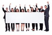 foto of stand up  - Group of stylish professional business people standing in a line holding up a long blank banner for your advertising or text - JPG