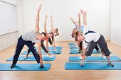 stock photo of pilates  - Large group of diverse people in a pilates class exercising in a gym doing core stretching - JPG