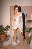 Phoebe Price preparing to go to the Emmys, wearing dress by Jean Fares Couture and headpiece by Phoe