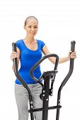 stock photo of elliptical  - Young woman uses elliptical cross trainer - JPG