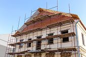 foto of scaffold  - Old historic building facade under reconstruction with scaffolding - JPG