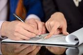 stock photo of statements  - Businessman and woman hand signing contract paper