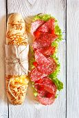 picture of sweetie  - Salami sandwich with lettuce and sweety drop peppers on a white wooden board - JPG