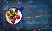 picture of yogurt  - Yogurt with granola and fresh berries on an old wooden board with copy space for text - JPG
