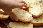 picture of bread rolls  - roll with butter on a plate with already buttered rolls sandwiches hand takes the bread - JPG