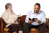 picture of bifocals  - A senior man and woman studying the Bible together on a sofa - JPG