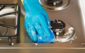 image of soapy  - Closeup horizontal image of hand wearing rubber glove while cleaning stove top range with soapy sponge - JPG