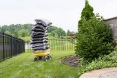 pic of manicured lawn  - Mulch in bags piled high on a cart in the garden teetering precariously as they wait to be spread over the flowerbeds in a carefully manicured rural garden - JPG