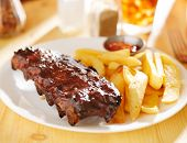picture of baby back ribs  - plate with barbecue ribs and french fries - JPG