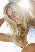 pic of blonde woman  - Stunningly beautiful young blond woman in backlit by sunshine and wearing a white bikini - JPG