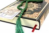 image of quran  - slammed Quran with Pakistani rupee before light background