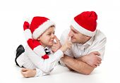 stock photo of tease  - Humour portrait of father man and son boy kid child in Santa - JPG