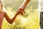 picture of children walking  - a parent holds the hand of a small child - JPG