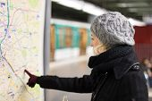 picture of orientation  - Casually dressed woman wearing winter coat, orientating herself with public transport map panel, pointing on her final destination. Urban transport.