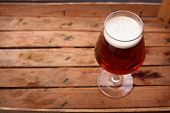 foto of crate  - Glass of amber beer standing in an old dirty wooden crate - JPG