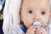 stock photo of nipple  - Cute baby with a nipple looking at camera - JPG