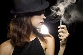 pic of tobacco smoke  - woman smoking or vaping an electronic cigarette to quit tobacco - JPG