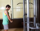 foto of pulley  - Triceps pressdown high pulley workout man at gym exercise - JPG