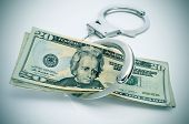 pic of bribery  - a pair of handcuffs and some dollar bills depicting the idea of arrest for bribery or corruption - JPG