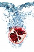 picture of pomegranate  - Fresh Pomegranate dropped into water with splash isolated on white - JPG