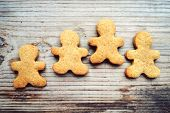 stock photo of gingerbread man  - Gingerbread cookies in shape of man on wooden table - JPG