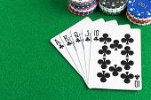 pic of poker hand  - A royal flush poker hand with chips and green felt table copy space - JPG