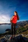 image of vest  - Sports woman in red vest with backpack standing on the top of mountain on the sunset - JPG