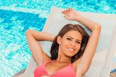 picture of woman bikini  - Top view of beautiful young woman in bikini relaxing on deck chair by the pool - JPG