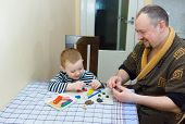 stock photo of molding clay  - the father and the son sit at a table and are engaged in a molding from color plasticine - JPG