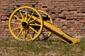 foto of cannon  - Replica of historic cannon standing on the grass in front of a brick - JPG