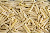 stock photo of hollow  - Background texture of penne rigate or ziti pasta with its hollow diagonally cut tubes used in Italian cuisine and for a tasty ziti casserole with cheese - JPG