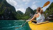 stock photo of kayak  - Woman exploring calm tropical bay with limestone mountains by kayak - JPG