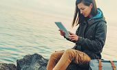 image of instagram  - Traveler girl sitting on coast near the sea and working on digital tablet - JPG