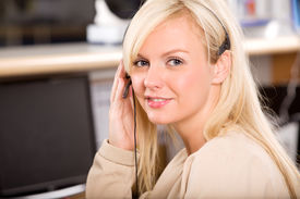 stock photo of medical office  - A happy friendly receptionist using a headset - JPG