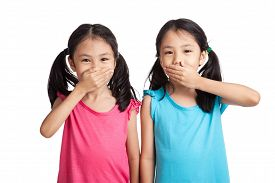 picture of identical twin girls  - Asian twins girls shut their mouth isolated on white background - JPG