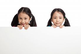 image of identical twin girls  - Happy Asian twins girls behind white blank banner on white background - JPG